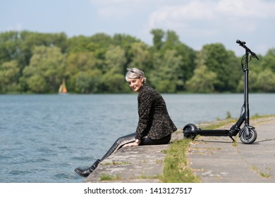 FRau with electric scooter takes a break at the lake