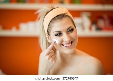 H�¼bsche Frau tr�¤gt Gesichtscreme auf