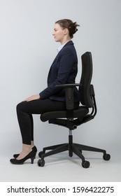 Frau im Blazer macht Übungen für gesu Business woman is sitting straiht up and correctly on an office chair to avoid tensions