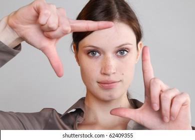 Frau schut durch die Finger.
