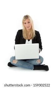 Frau sitzt mit Laptop am Boden