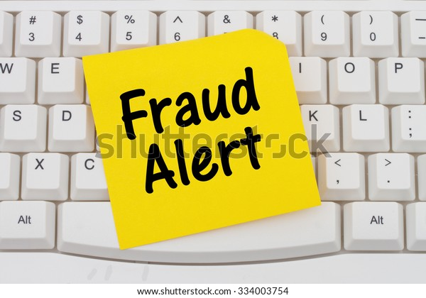 Fraud Alert, Computer Keyboard with a yellow blank sticky note with text Fraud Alert