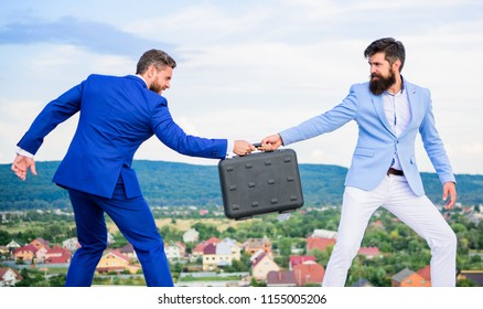 Fraud and extortion concept. Rascal racketeer extortionist cheating handover. Men suits handover briefcase. Business deal landscape background. Businessman takes away briefcase from business partner.