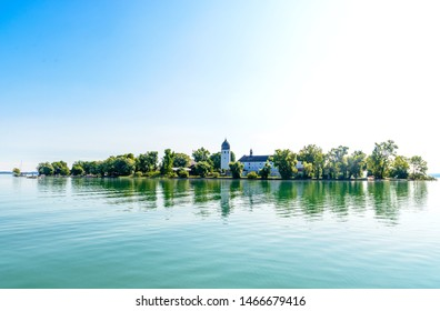 Fraueninsel, Frauenchiemsee on lake Chiemsee in the  morning sunrise with boat, Sailboat, church, monastery. Bavaria, Bayern, Germany