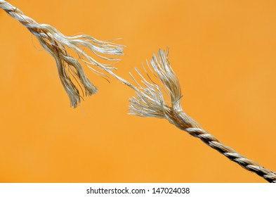 Frayed rope about to break. Isolated over yellow