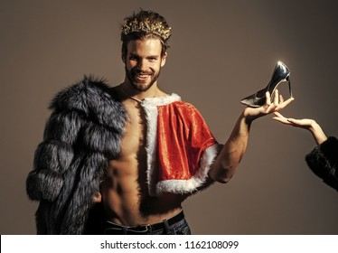 Freak, gay and transvestite. Christmas guy in santa fur coat in crown. Cinderella prince with shoe on grey background. Drag queen, homosexual and trans.