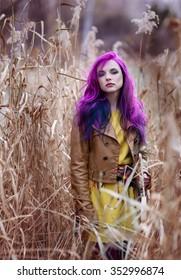 Freak girl with purple hair in high autumn grass