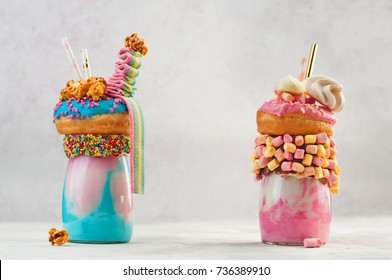 Freak shakes topping with donut, marshmallow, meringues, popcorn and marmalade on grey background with copy space