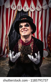 Freaking out magician in magician hat and black outfit shows his dark face on the scene of the dark circus