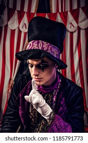 Freaking out magician in magician hat and black outfit shows silence gesture on the scene of the dark circus
