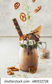 Freakshake topping with whipped cream and ice cream waffle cone on light background; selective focus. Levitation of sprinkles and pretzel ingredients.