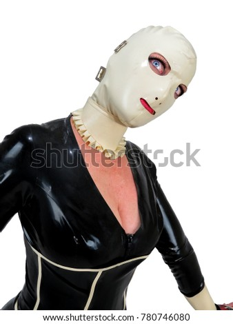 Freaky hooded cosplay woman in black latex rubber catsuit and cream hood. Big blue staring eyes. Creepy doll fetish costume. Portrait with white background.