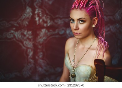 Freaky young female model in vintage luxury clothing wearing corset with golden ornament. Bright pink dreadlocks hairstyle, beauty make up.