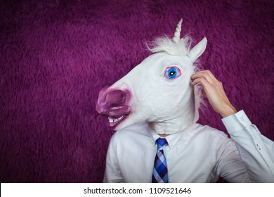 Freaky young man in comical mask stands on the purple background. Portrait of unusual manager. Confused unicorn in shirt and tie is thinking