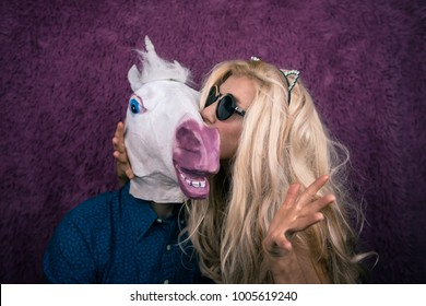 Freaky young woman in sunglasses and kitty ears kissing happy unicorn on the purple background. Expressive blond with strange guy. Unusual people sits together and shows emotions.