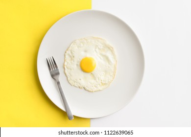 Freashly cooked egg on white plate centered over split color yellow/white background.