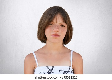 Freckled girl with hazel eyes and dark short hair, looking with displeasure into camera while posing against whiye concrete wall. Beautiful little girl with stylish hairdo wearing summer dress
