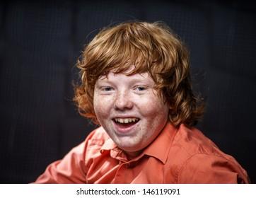 Freckled red-hair boy posing on dark background. Emotions.
