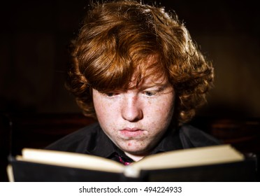 Freckled red-haired teenage boy reading book, education concept, isolated on black background
