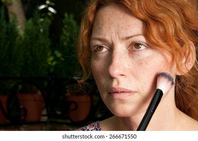 freckled woman putting morning makeup