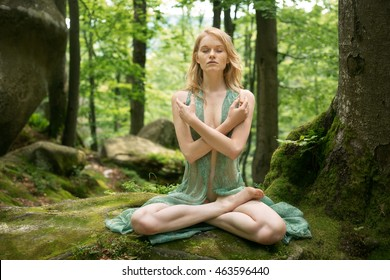 Freckles, red-haired woman meditating and doing yoga  in fairy forest
