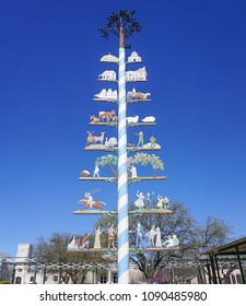 FREDERICKSBURG, TEXAS: MARCH 7, 2018 - Colorful Maypole in Marktplatz Park erected in 1991 with symbols representing the town's history and an Autumn Ocktoberfest celebration.
