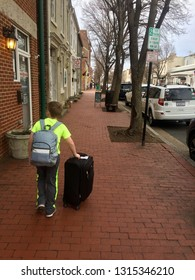 Fredericksburg, Virginia, USA - February 15, 2019: A boy pushes his luggage on a brick sidewalk enroute to his hotel in the historic district of this popular tourist destination.