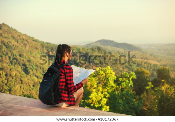 Free beautiful girl traveler sitting with his back to the camera and reading a map on the background of the mountains, human and nature.