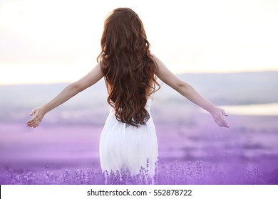 Free brunette woman with open arms enjoying sunset in lavender field. Harmony. Attractive girl with long curly hair style in white dress dreaming.