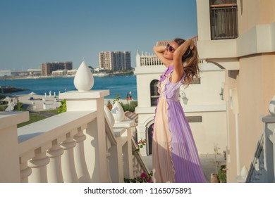 Free carefree happy girl in beautiful dress standing in balcony and looking at sun.