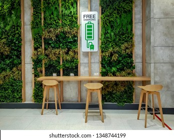 Free Charging Station with green and natural decoration and some wooden stools in public waiting area inside office building.