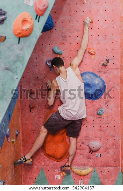 Free climber young man climbing artificial boulder indoors, back view