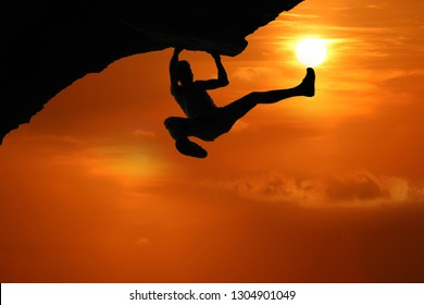 Free climbing on the mountain at red sky sunset background,Silhouette of asian man climbing rock