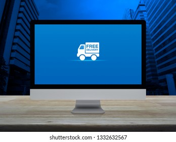 Free delivery truck flat icon on desktop modern computer monitor screen on wooden table over office city tower and skyscraper, Business transportation online concept