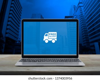 Free delivery truck flat icon with modern laptop computer on wooden table over office city tower and skyscraper, Business transportation online concept