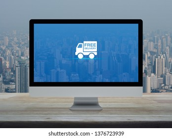 Free delivery truck flat icon on desktop modern computer monitor screen on wooden table over office building tower and skyscraper in city, Business transportation online concept