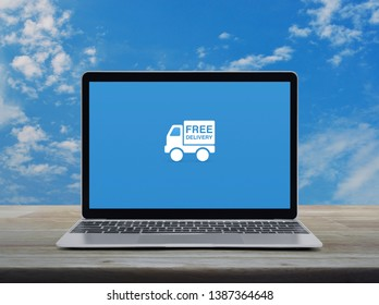 Free delivery truck flat icon with modern laptop computer on wooden table over blue sky with white clouds, Business transportation online concept