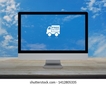 Free delivery truck flat icon on desktop modern computer monitor screen on wooden table over blue sky with white clouds, Business transportation online concept