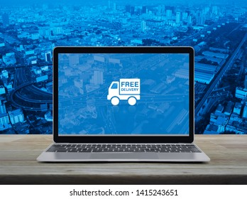 Free delivery truck flat icon with modern laptop computer on wooden table over city tower, street, expressway and skyscraper, Business transportation online concept