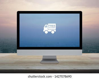 Free delivery truck flat icon on desktop modern computer monitor screen on wooden table over city tower and skyscraper at sunset sky, vintage style, Business transportation online concept