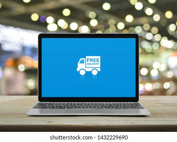 Free delivery truck flat icon with modern laptop computer on wooden table over blur light and shadow of shopping mall, Business transportation online concept