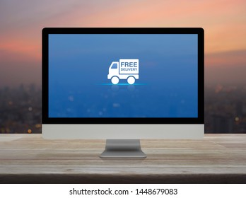 Free delivery truck flat icon on desktop modern computer monitor screen on wooden table over blur of cityscape on warm light sundown, Business transportation online concept