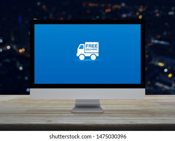 Free delivery truck flat icon on desktop modern computer monitor screen on wooden table over blur colorful night light city tower and skyscraper, Business transportation online concept