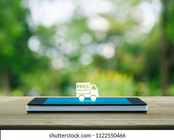Free delivery truck icon on modern smart phone screen on wooden table over blur green tree in park, Transportation business concept