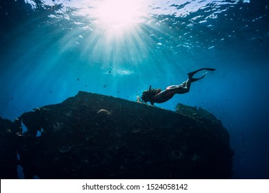 Free diver girl in pink swimwear with fins swimming underwater at wreck ship. Freediving in the ocean