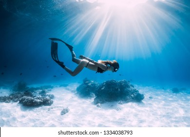 Free diver glides over sandy sea with fins. Freediving in blue ocean