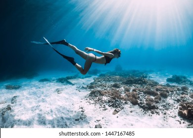 Free diver glides over sandy sea with fins. Freediving in blue sea