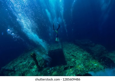 Free diver man dive at shipwreck, underwater