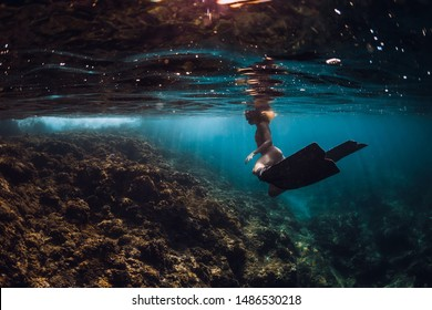 Free diver young woman with fins over coral bottom. Freediving underwater in ocean