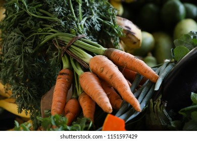 Free Fair. Carrots in the foreground, with fruits and vegetables in the background.